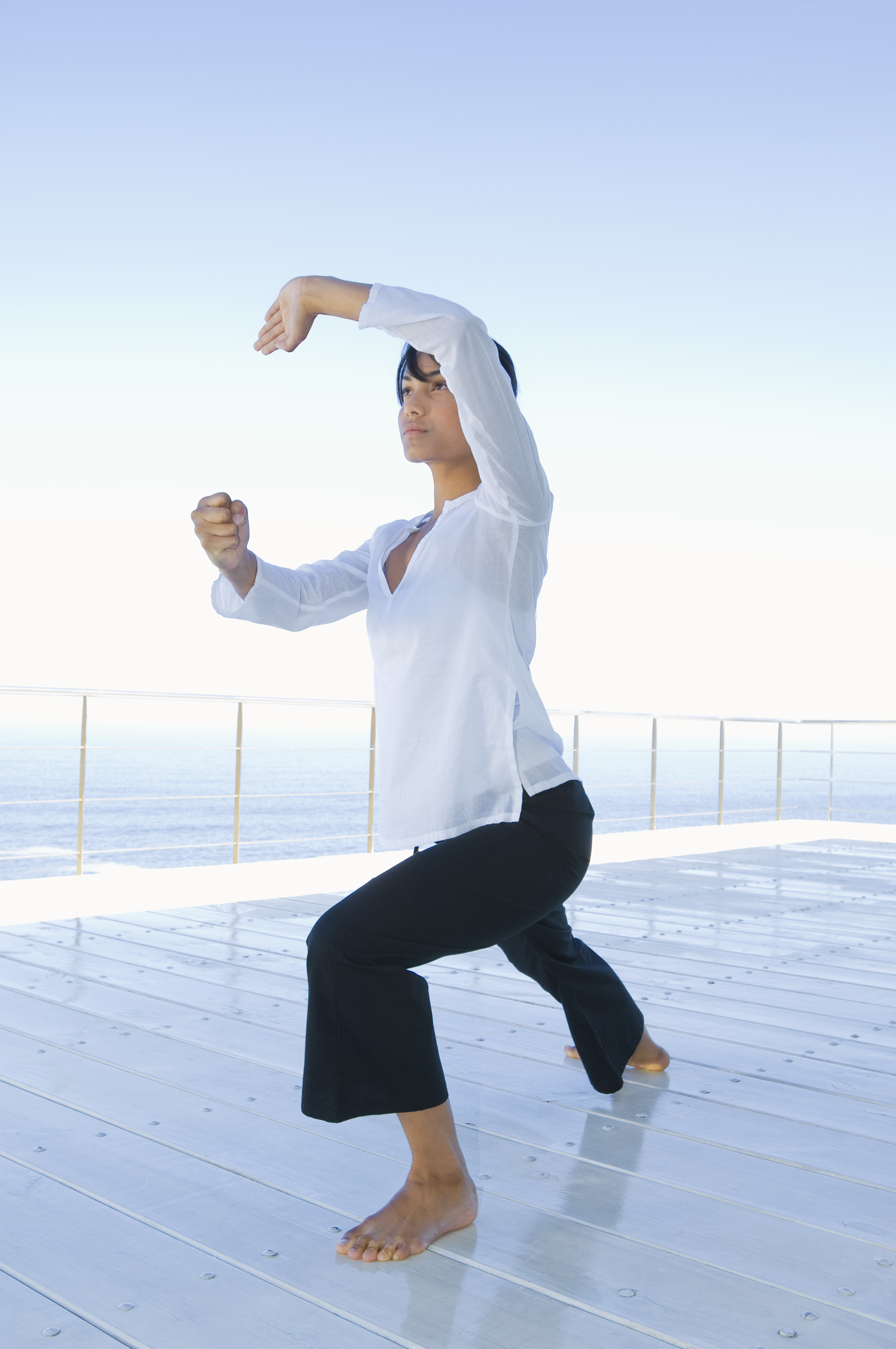Woman practicing Tai Chi on deck